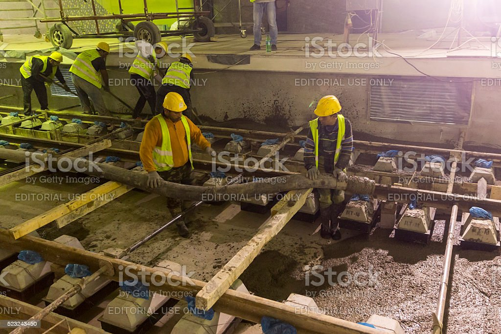 Underground subway tunnel workers pouring concrete stock photo