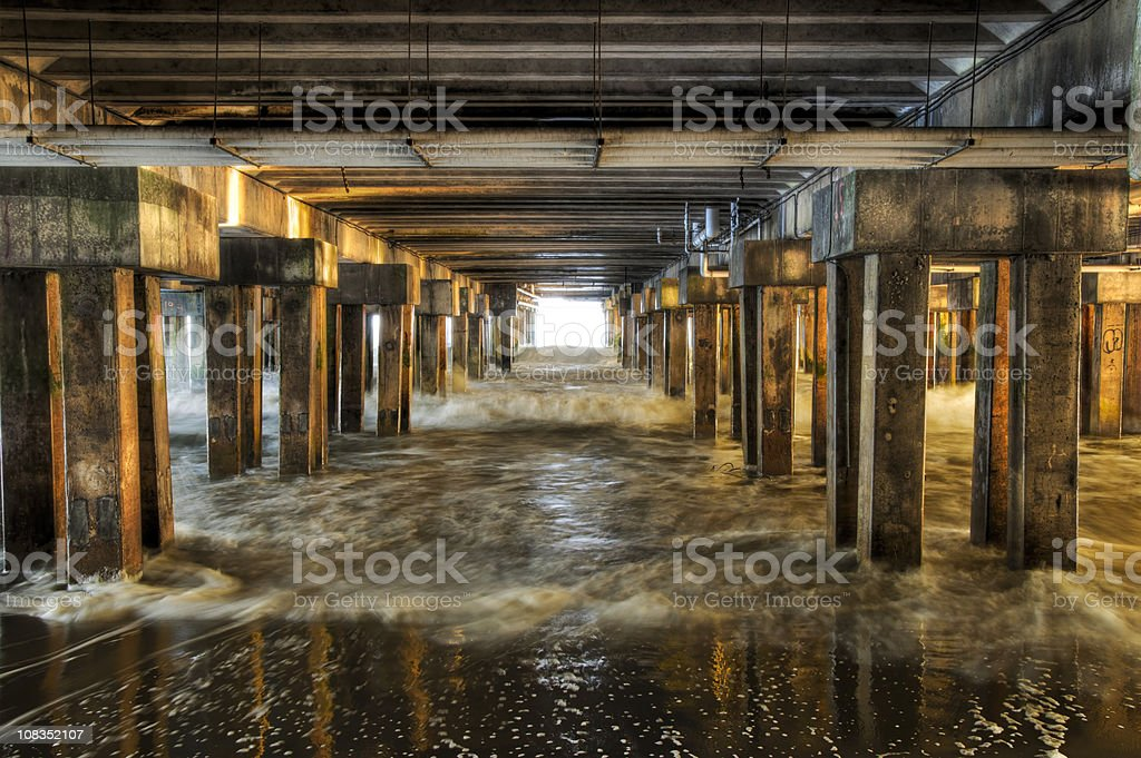 Underneath a pier at sunset stock photo