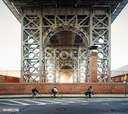 Underneath the Brooklyn Williamsburg bridge in the morning with out of focus bikers commuting.