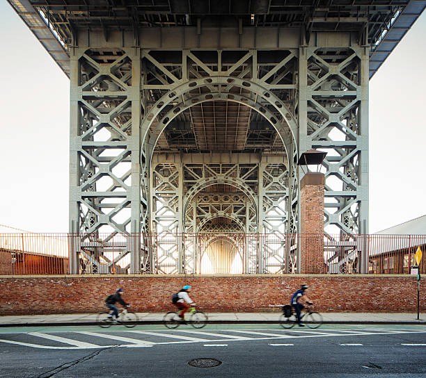 underneath the brooklyn williamsburg bridge morning with bikers - lower east side manhattan stock pictures, royalty-free photos & images