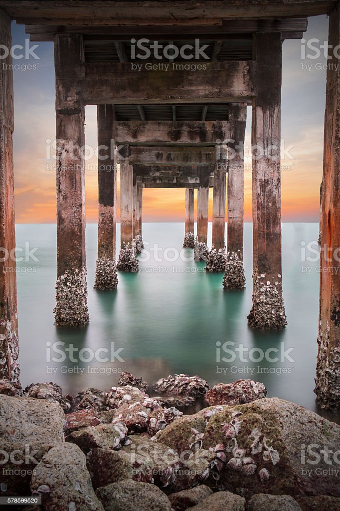 Underneath the pylons of a long jetty pier beach stock photo