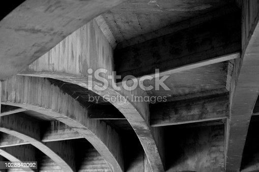 Underneath of a highway overpass showing detailed lines and shadows