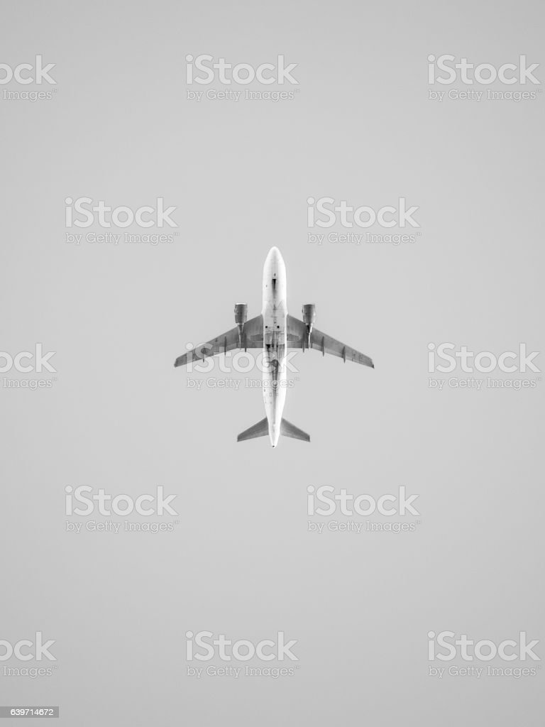 Underside of a commercial jet plane, isolated against grey background stock photo
