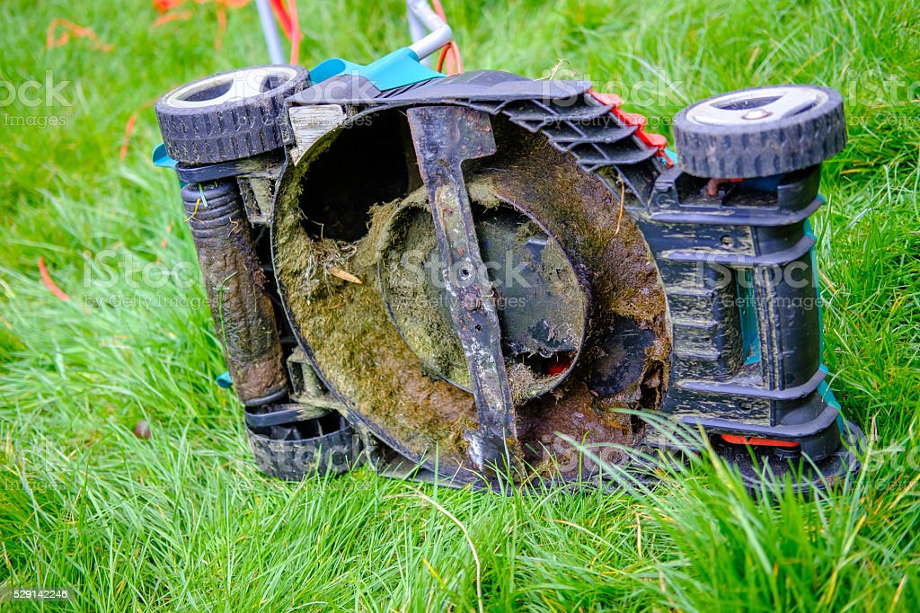 Underside of a Lawn Mower in long grass stock photo