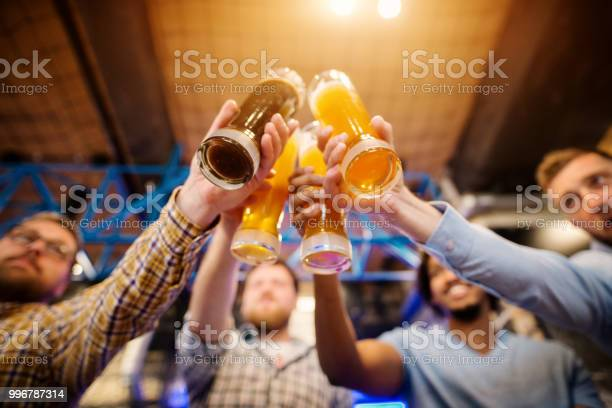 Underside view of draft beer glasses while four male friends clinking picture id996787314?b=1&k=6&m=996787314&s=612x612&h=rklmt75eq8t9amyk3uprnxkfjzabionr5rejxpp6yba=