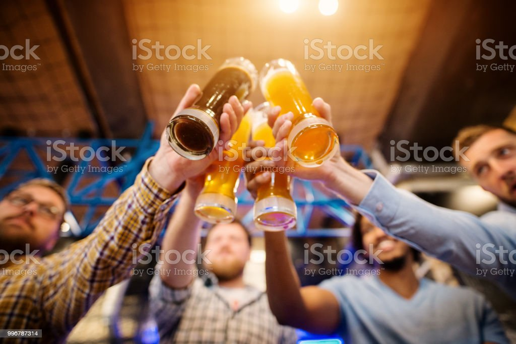 Underside view of draft beer glasses while four male friends clinking in the pub. stock photo
