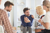 istock Understanding mature psychiatrist with curly hair touching shoulder of patient and supporting him while helping him to cope with addiction at group counseling therapy 1066709922