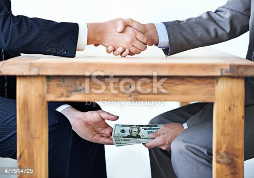 Cropped shot of two businessmen shaking hands while money passes hands under a table