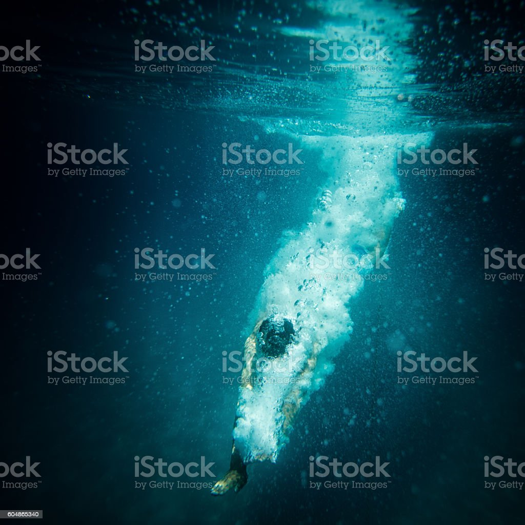 Underwater action shot of diver breaking water surface stock photo