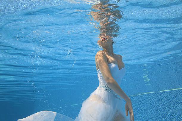 underwater  ballet    woman ballerina dancing under the water   swimming pool - meerjungfrau kleid stock-fotos und bilder