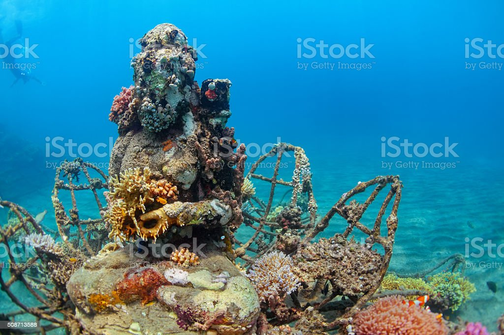 Underwater Buddha statue with diving snorkeler on the background0122 Buddha statue on sea sand bottom on background of snorkeler swimming deep down into water to observe tropical reef. Vacation adventures and underwater safari on scuba diving sites in Bali, Indonesia. Activity Stock Photo