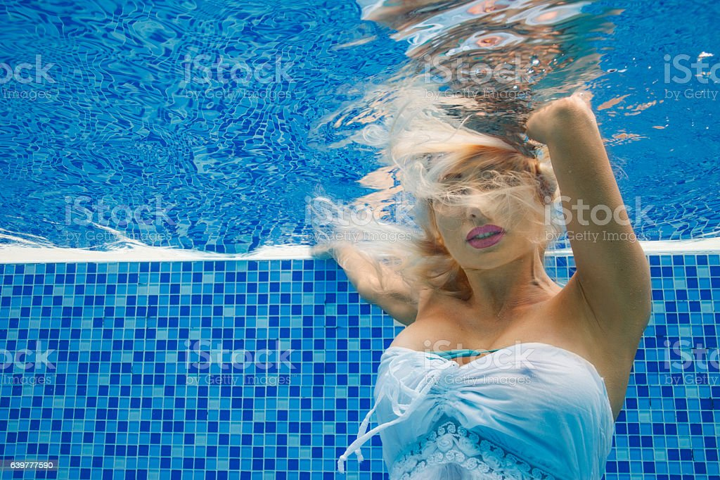 Smiling young woman underwater in a pool — long hair