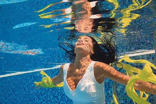 Girls swim underwater at a pool party Stock Photo