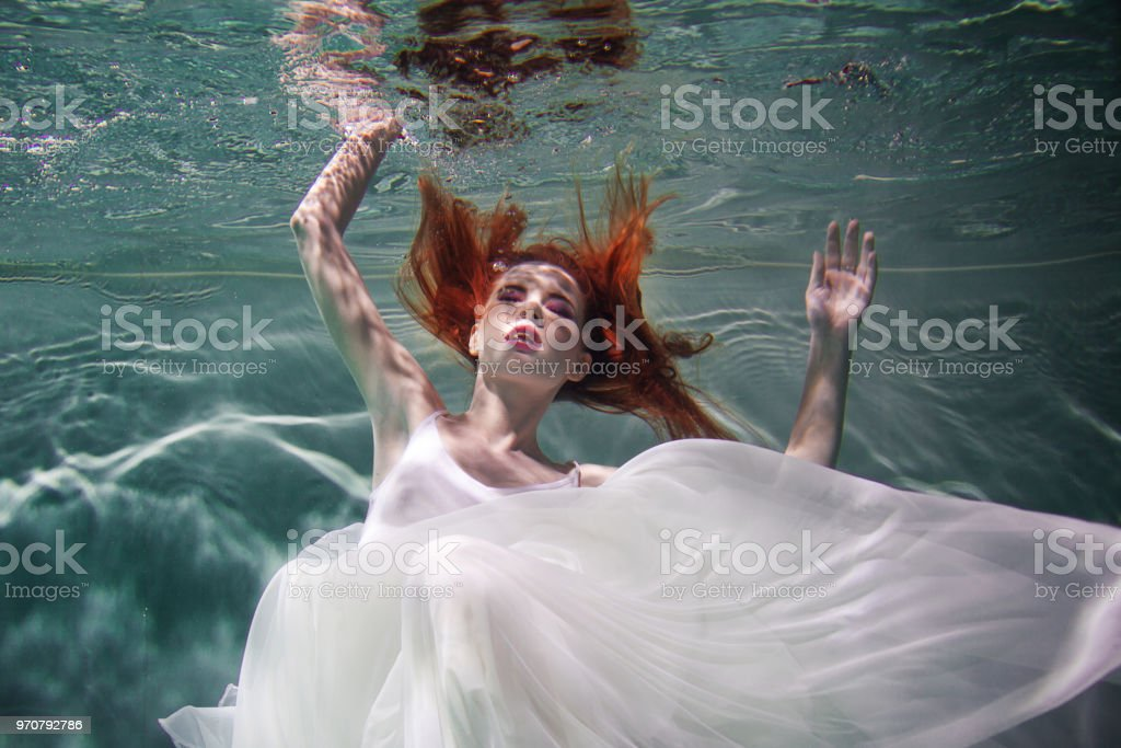 Rothaariges Mädchen Privsem im roten Seidenkleid zeigt nackten Körper unter Wasser