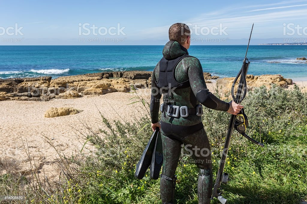Underwater hunter with a gun in mask. stock photo