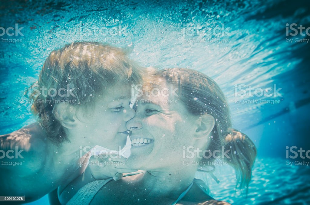 Underwater kisses selfie with mom and son in a pool stock photo