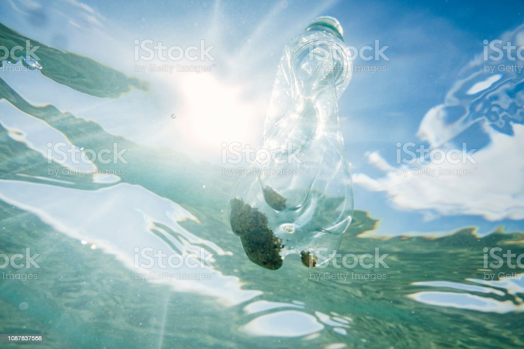 Underwater looking upwards to the sea surface with suspended used plastic water bottle. stock photo