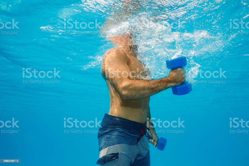 Underwater   Mid adult man training  with dumbbells  in swimming pool royalty-free stock photo