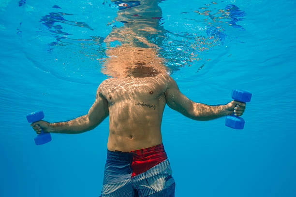 Underwater   Mid adult man training  with dumbbells  in swimming pool stock photo