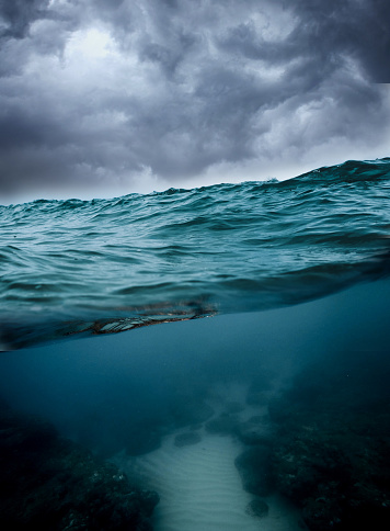 Underwater, ocean with cloudy sky and reef