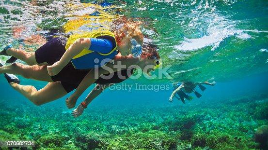 831127716 istock photo Underwater photo. Happy family snorkelling in tropical sea 1070602734