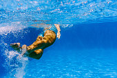 Underwater photo of a woman swimming in deep blue water. Rear view