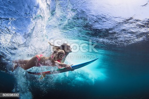 istock Underwater photo of girl with board dive under ocean wave 505098332