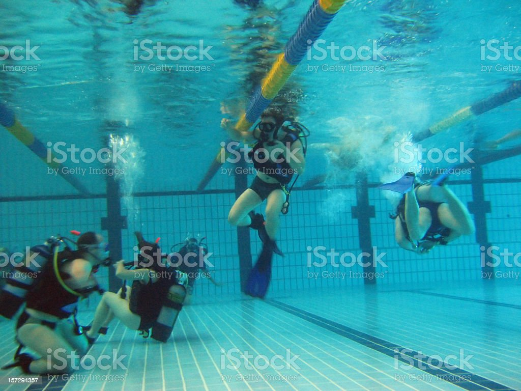Underwater photo of people scuba diving in a swimming pool
