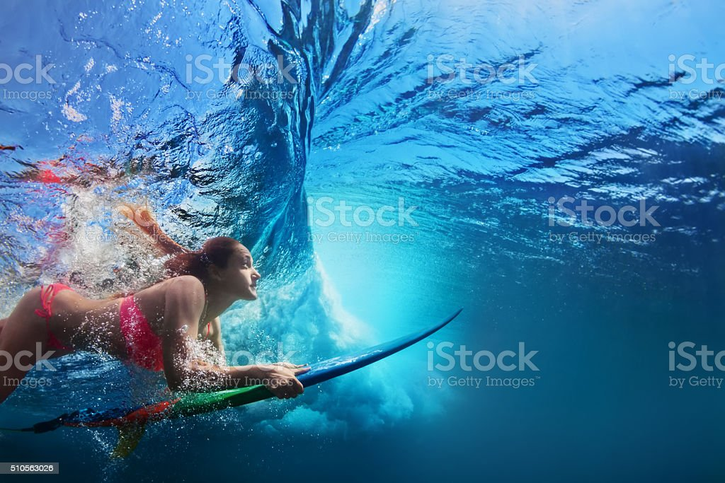 Underwater photo of surfer girl diving under ocean wave stock photo