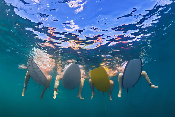Underwater photo of surfers sitting on surf boards stock photo