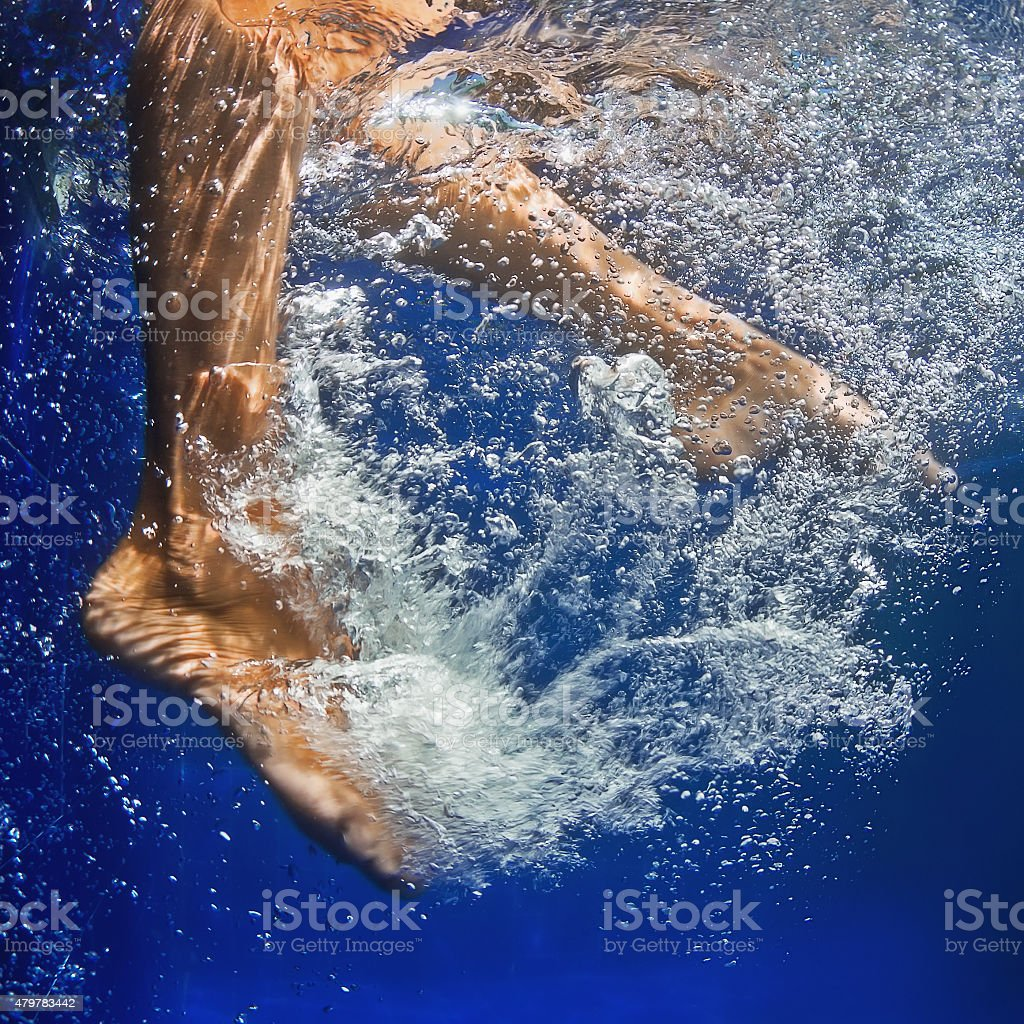 Underwater photo of the women legs in the pool stock photo