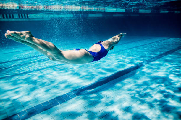 underwater picture of young female swimmer exercising in swimming pool - swimming stock pictures, royalty-free photos & images