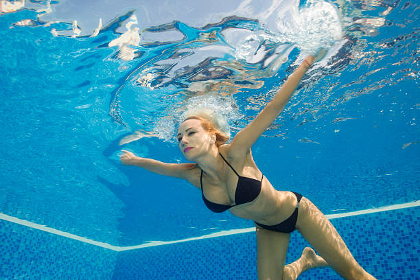 Underwater Pool party  Woman swimming relaxing in swimming pool Pool party. Underwater,  woman swimming, diving  relaxing in swimming pool. Summer fun  in water. middle aged women in bikinis stock pictures, royalty-free photos & images