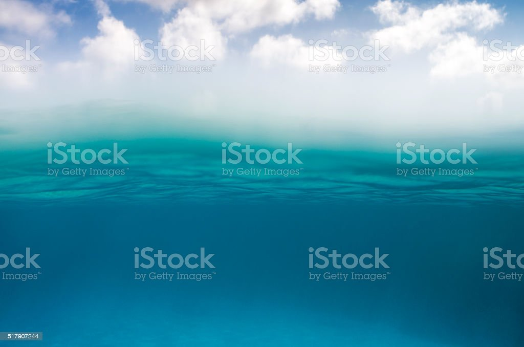 Underwater scene in bottom and sky with clouds on top stock photo