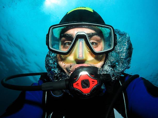 Underwater scuba diver making self portrait or selfie. stock photo