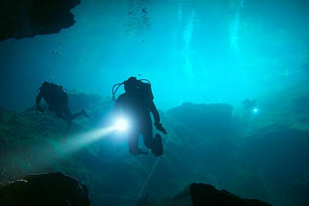 Underwater scuba divers in a cenote stock photo