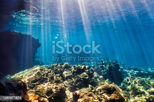 The scene from underneath the Andaman Sea.  The location is the famous destination Ko Haa Island 3, Krabi province, Thailand.  Stunning limestone Karst Islands rise up from the Andaman Sea.  Famed for their stunning coral reefs.  A popular site with Scuba Divers and Snorkelers.  Here we see the morning sunbeams piercing the blue sea onto the coral reef.  An ideal background image.  Sony mirrorless camera used in underwater housing.
