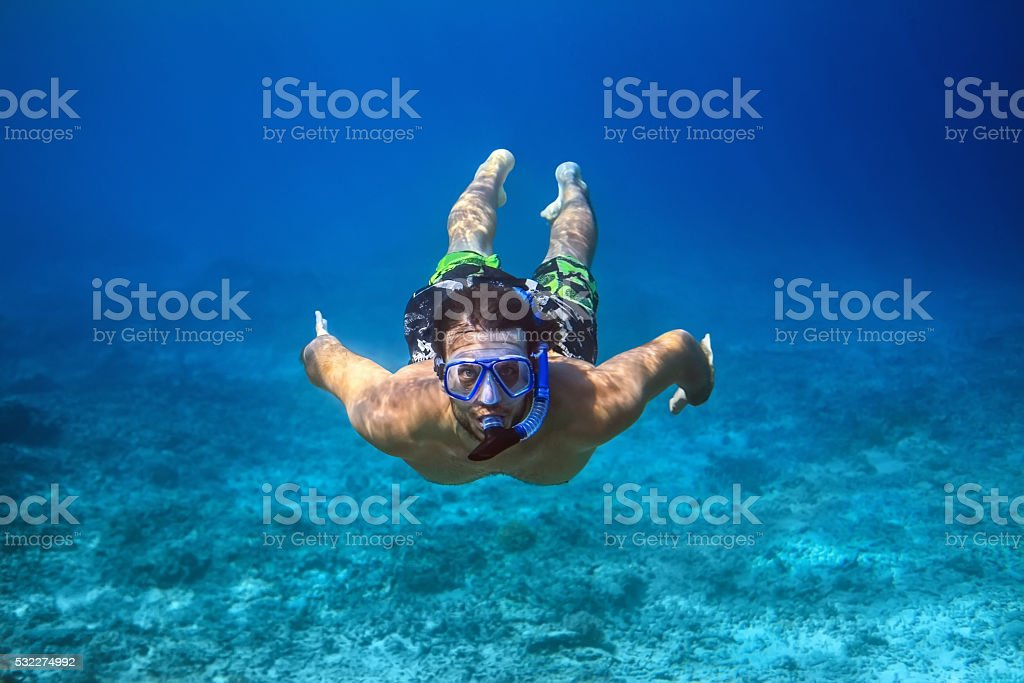 Underwater shoot of a young man snorkeling in tropical sea stock photo