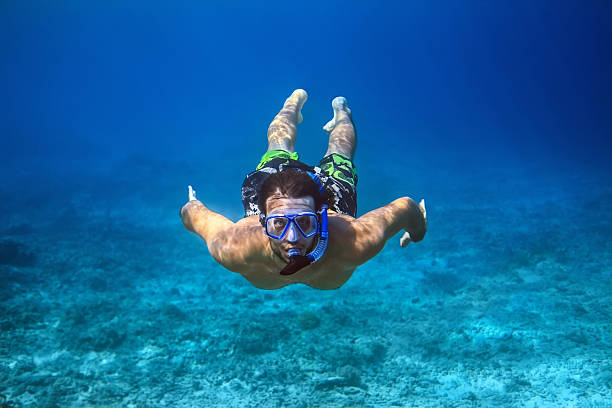 Underwater shoot of a young man snorkeling in tropical sea Underwater shoot of a young man snorkeling in a tropical sea. vacation concept snorkel stock pictures, royalty-free photos & images