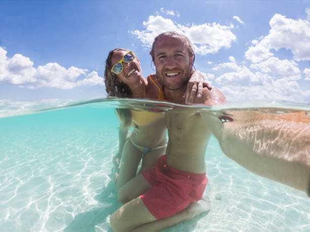 Underwater shot of couple taking selfie on idyllic beach stock photo