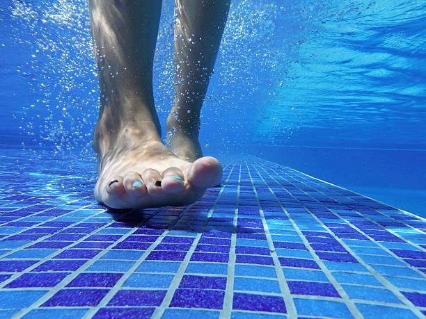 underwater shot of feet on pool bottom - pool schritte stock-fotos und bilder