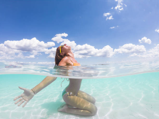 Underwater shot of woman relaxing on idyllic beach arms outstretched stock photo