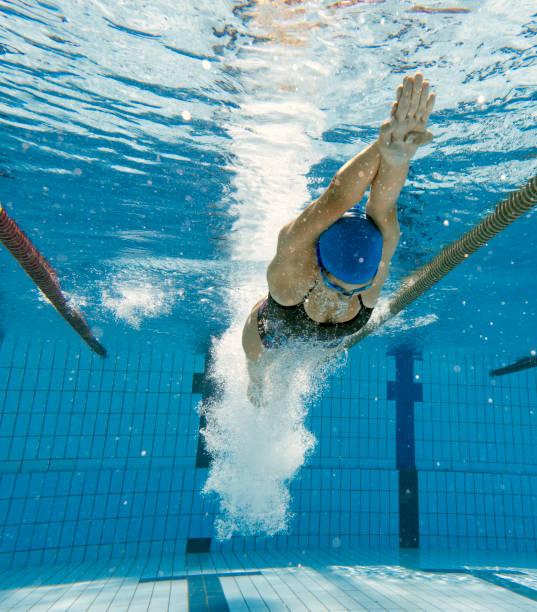 onderwater schot van jonge vrouwen duiken in het water en de race start - wedstrijdsport stockfoto's en -beelden
