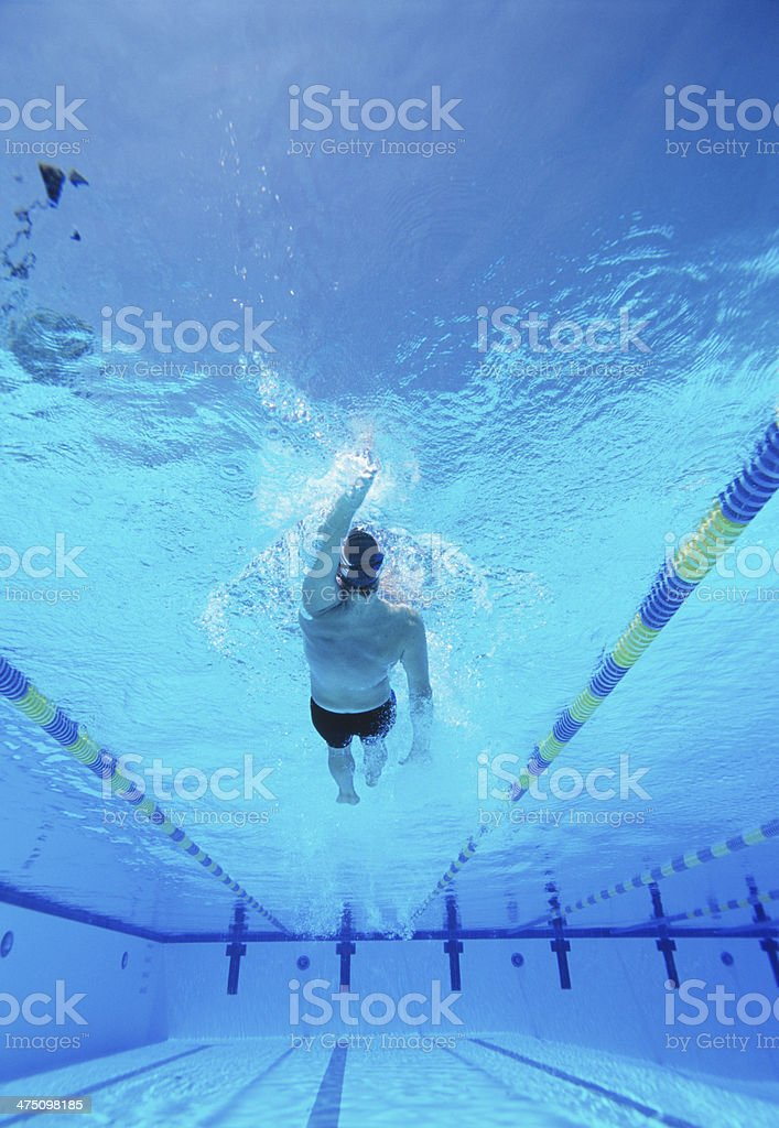 Underwater shot young male athlete doing backstroke in swimming pool stock photo