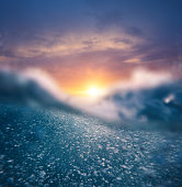 Underwater view on a splashing wave at sunset (combined underwater and surface view).