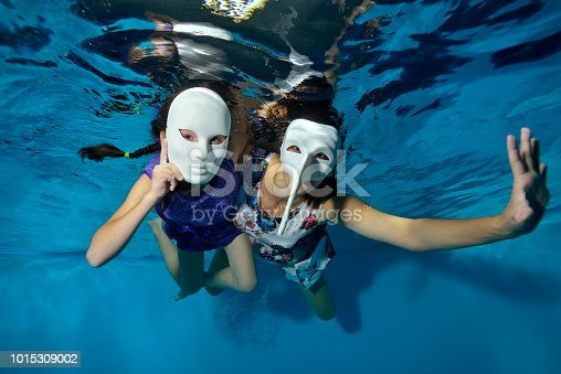Mom-coach with two children-little girls, swim and play underwater on a blue background in Santa's hats. They hold toys in their hands, look at the camera and smile. Portrait.