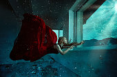 Side view of blonde fashion model swimming underwater in her red dress, fantasy concept