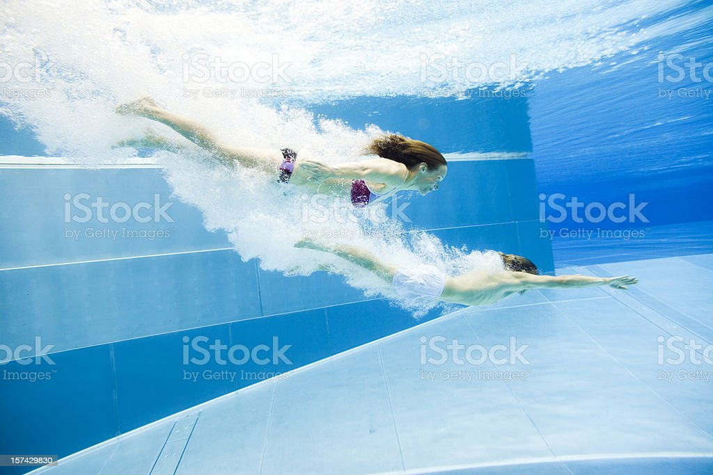 underwater view of a young couple jumping into the water royalty-free stock photo