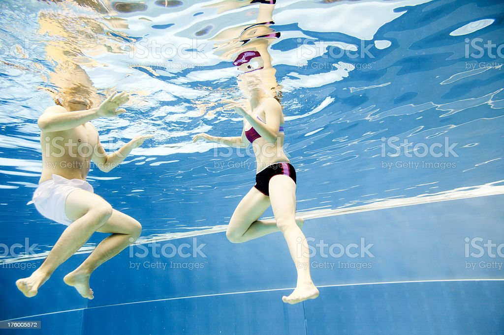 underwater view of a young couple swimming in the pool royalty-free stock photo
