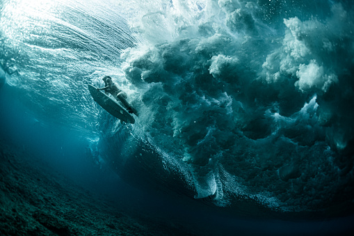 Underwater view of the woman surfer passing the powerfull ocean wave